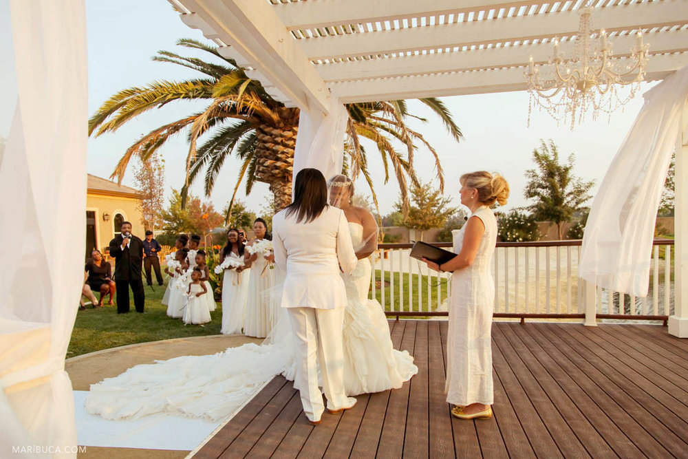 Adorable bride and groom, and white wedding theme around during the wedding ceremony in the Newberry Estate Vineyards.