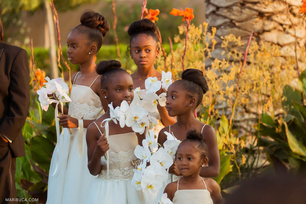 Beautiful flower girls with white dresses hold white big flowers and listen the wedding ceremony.