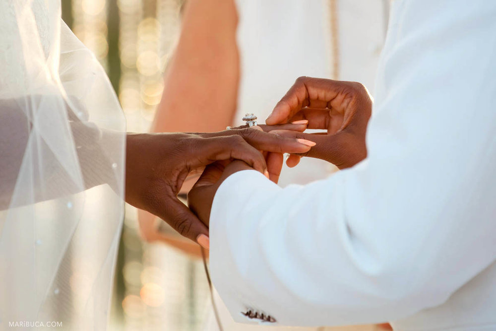 the groom put the wedding ring on the bride's finger