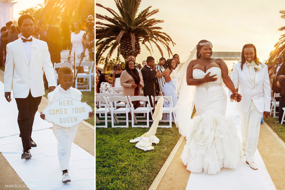 """Newlyweds couple are leaving the ceremony and the Barrier Rings with sign """"Here Comes your Queen"""" with yellow-orange rays during sunset time in the Newberry Estate Vineyards."""