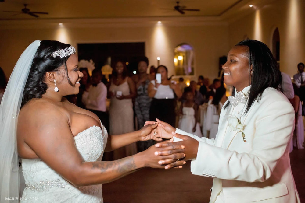 The groom and the bride look each other in the first dance wedding. Same sex wedding.