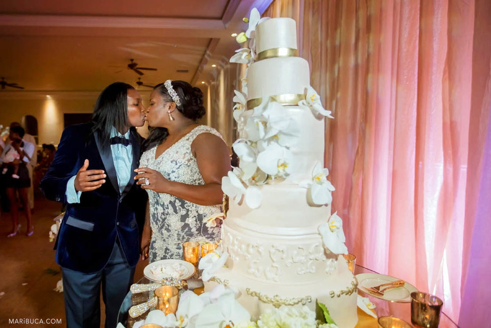 Groom and bride are kissing next the big five levels wedding cake and the pink curtains in the same sex wedding.