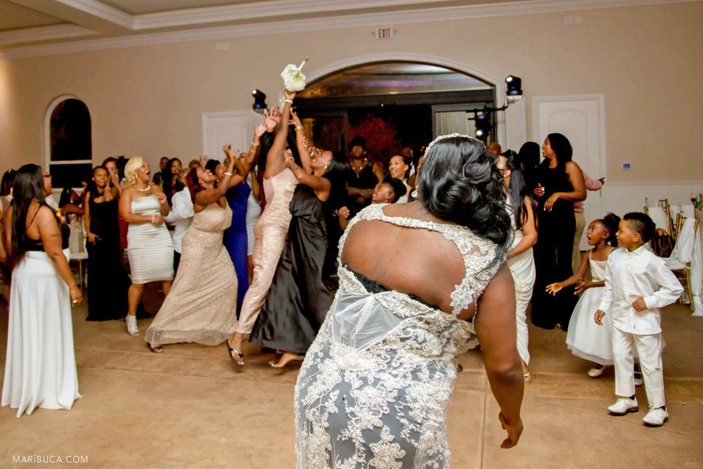 Girls try to catch wedding bouquet in the same sex wedding.