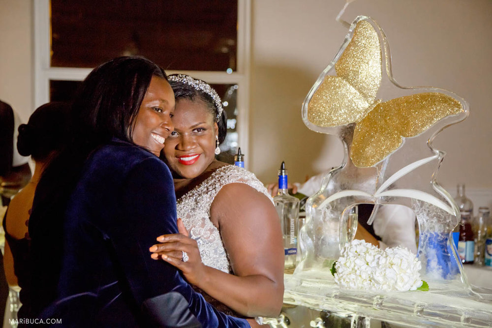 Groom and bride hug and smile next to ice bar with golden butterfly in the indoor girls wedding