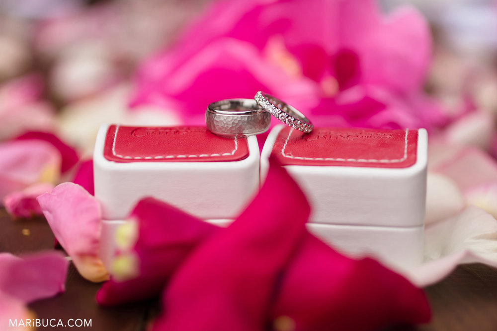 wedding rings lay down on the red boxes surrounded pink rose petals