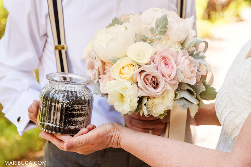 Wedding details such as  wedding bouquet, glass vase with black sands and newlywed's hands