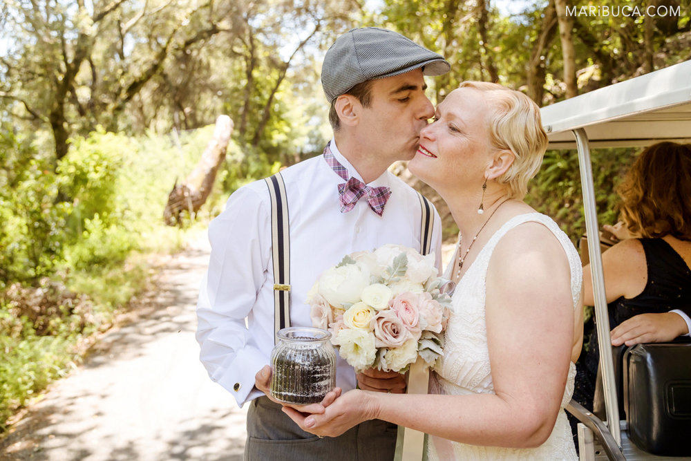 the groom kiss her lovely bride in the cheek outdoor wedding in the Los Gatos