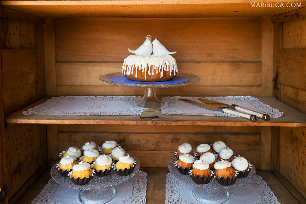 Wedding cake with adorable white lovely two pigeons and wedding cupcakes stay in the shelves.