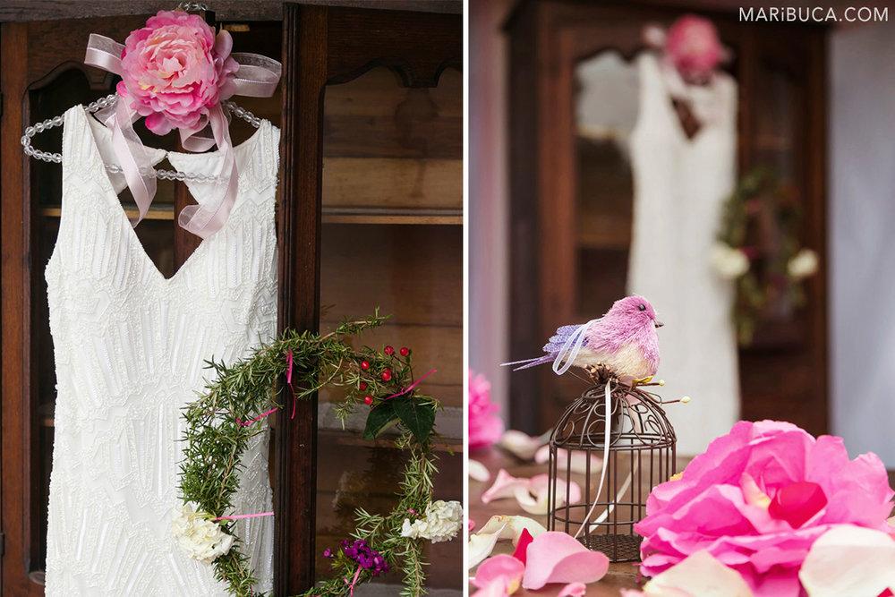 Wedding detail: The white wedding dress, pink flowers and bird decoration.