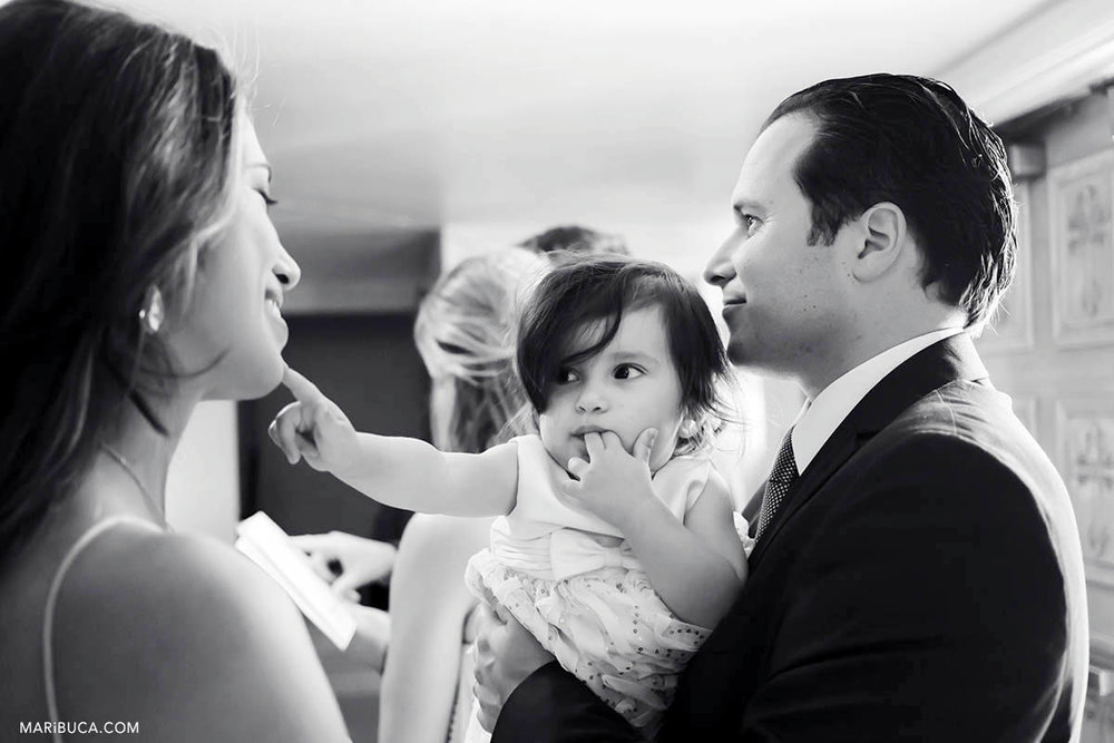 Black and white image. The baby girl is touching mom and mother smiling. Dad is listening the priest during baptism ceremony.
