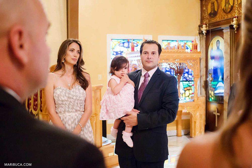 Adorable two years baby girl with family and guests during christening baptism in the San Jose Greek Orthodox Christening in St Nicholas church