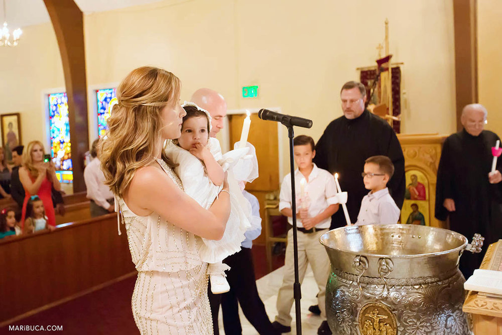 The godmother holds baby girl surrounded kids and the priest in the San Jose Greek Orthodox Christening