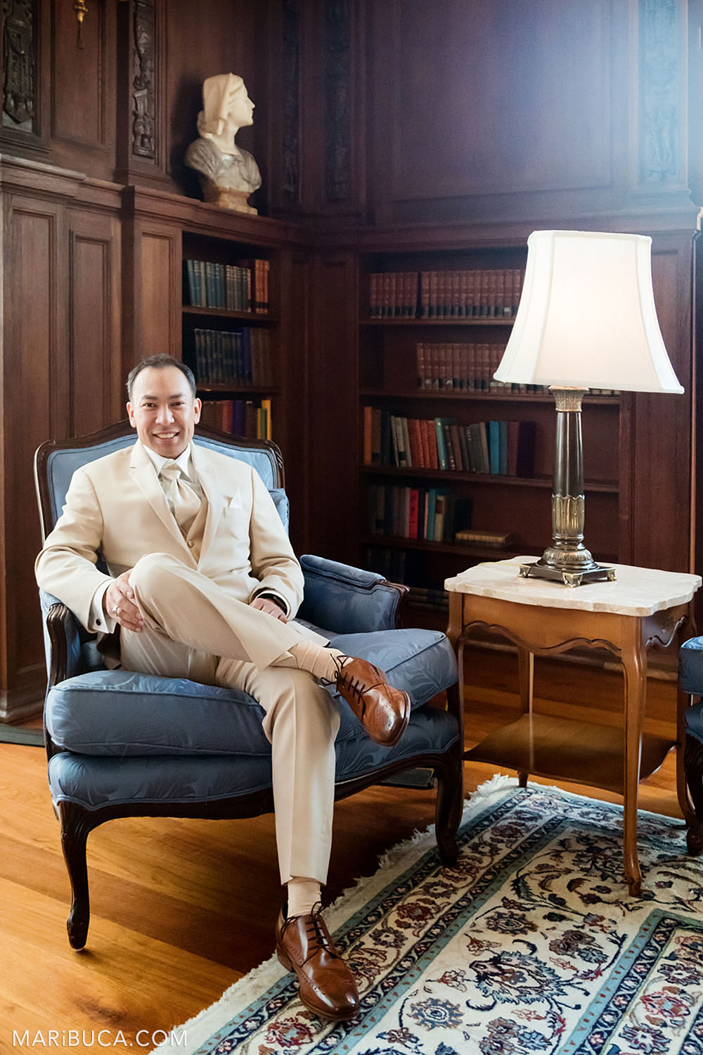 The groom smiles and sits in the Library during getting ready in the Kohl Mansion, Burlingame