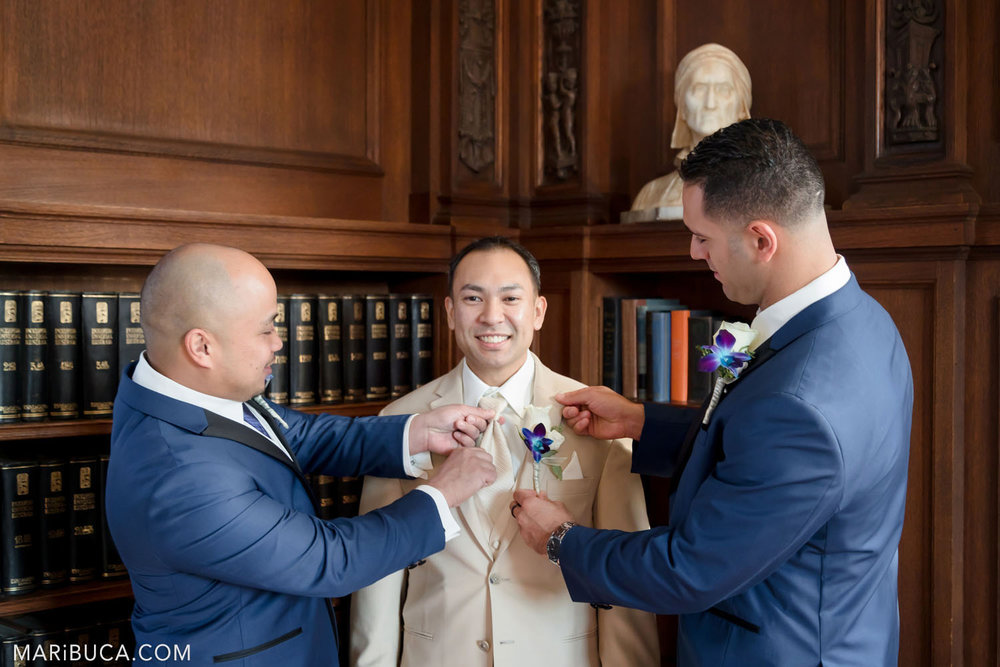 Groomsmen helps groom with last touch during getting ready surrounded old books in the Library Kohl Mansion Wedding