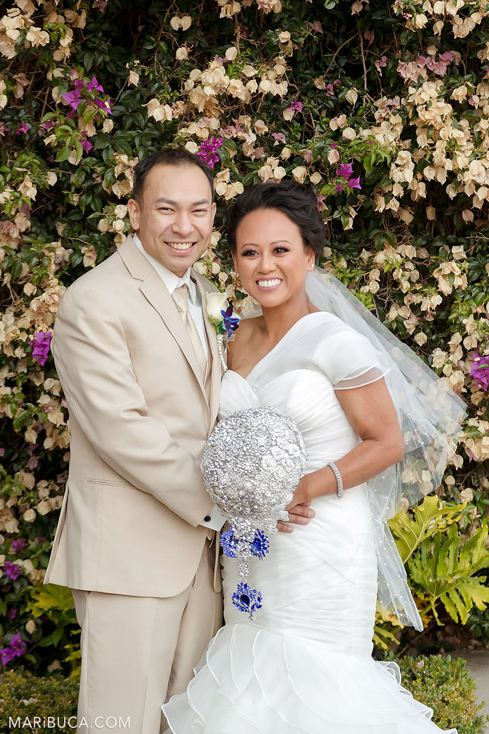 bride and groom stand in an embrace and smile surrounded by flowers