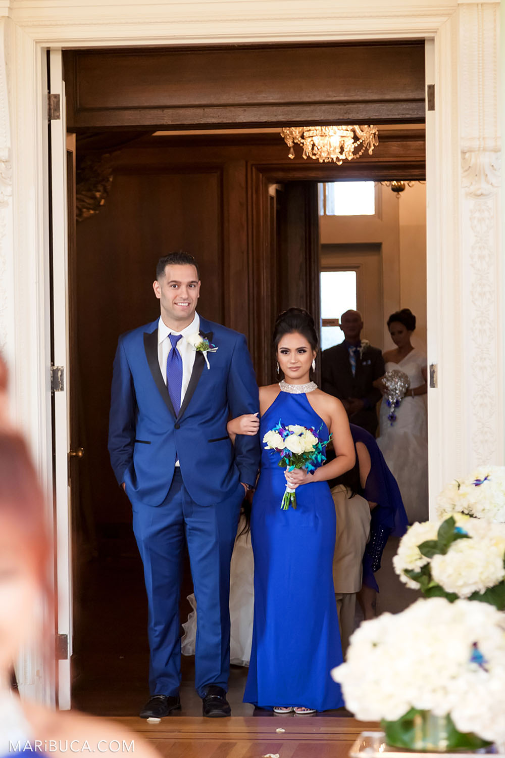 Groomsmen and bridesmaid with blue cloths are going down the aisle in the Dining room, Kohl Mansion Wedding ceremony