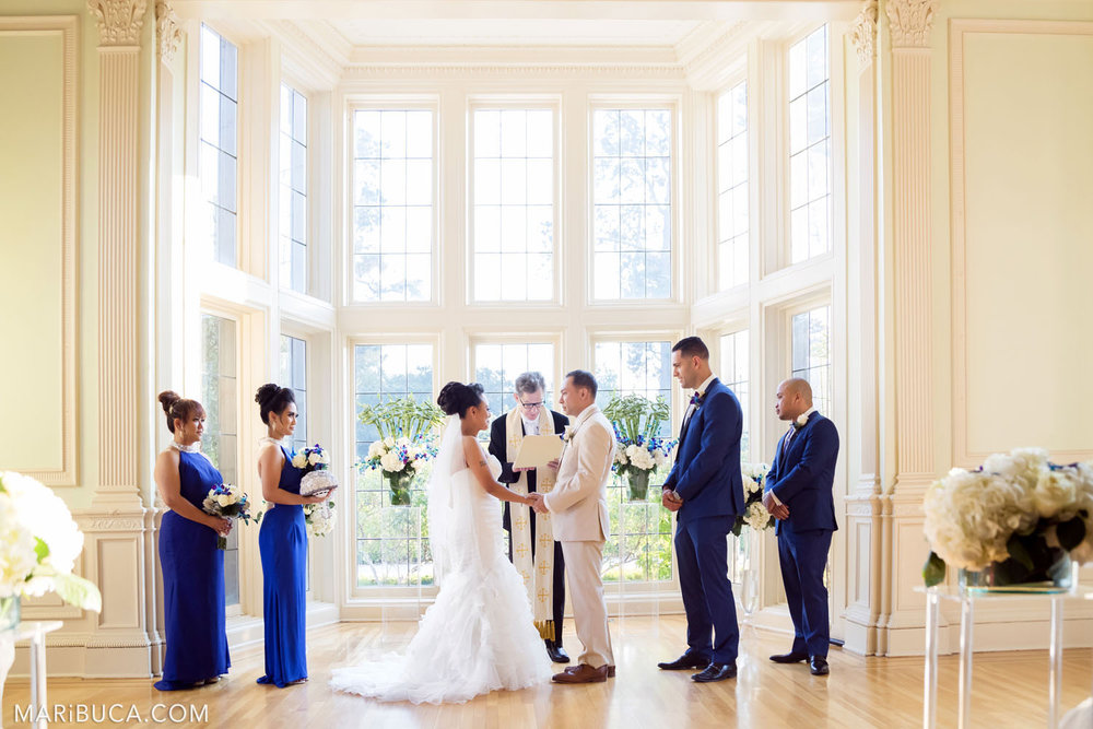 The wedding ceremony begins in the Dining room, Kohl Mansion Wedding. White bouquets of flowers and walls.