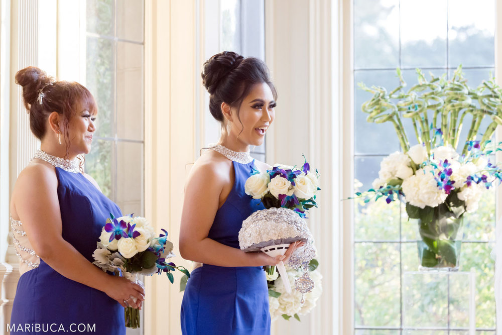Bridesmaids with navy blue dresses look to the bride and groom in the wedding ceremony.