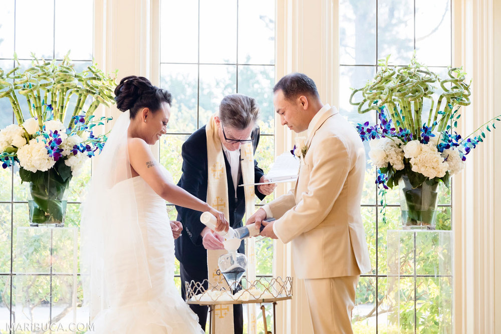 The bride and the groom are doing the sand ceremony as creating the new one family in the Dining room, Kohl Mansion Wedding, Burlingame.