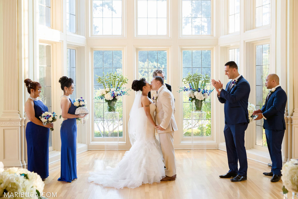 First kiss as newlyweds couple and wedding party excited and happy for them in the Dining room, Kohl Mansion Wedding, Burlingame.