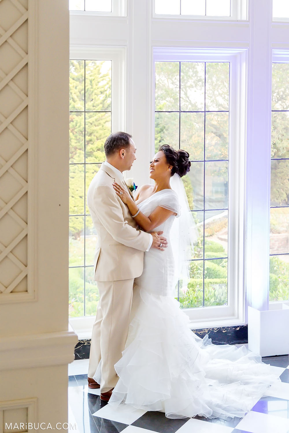 Groom and bride smile and stay in front of big windows with an amazing view inside in the Morning Room, Kohl Mansion, Burlingame