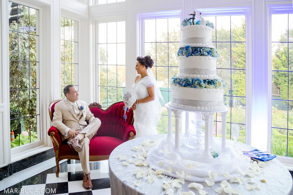 The bride and groom communicate with the other one on a background of the red couch and white big wedding cake with blue roses in the Morning Room, Kohl Mansion, Burlingame