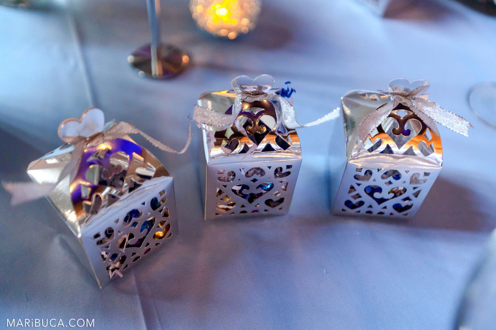 Wedding details: Light blue background, three boxes with gifts for guests