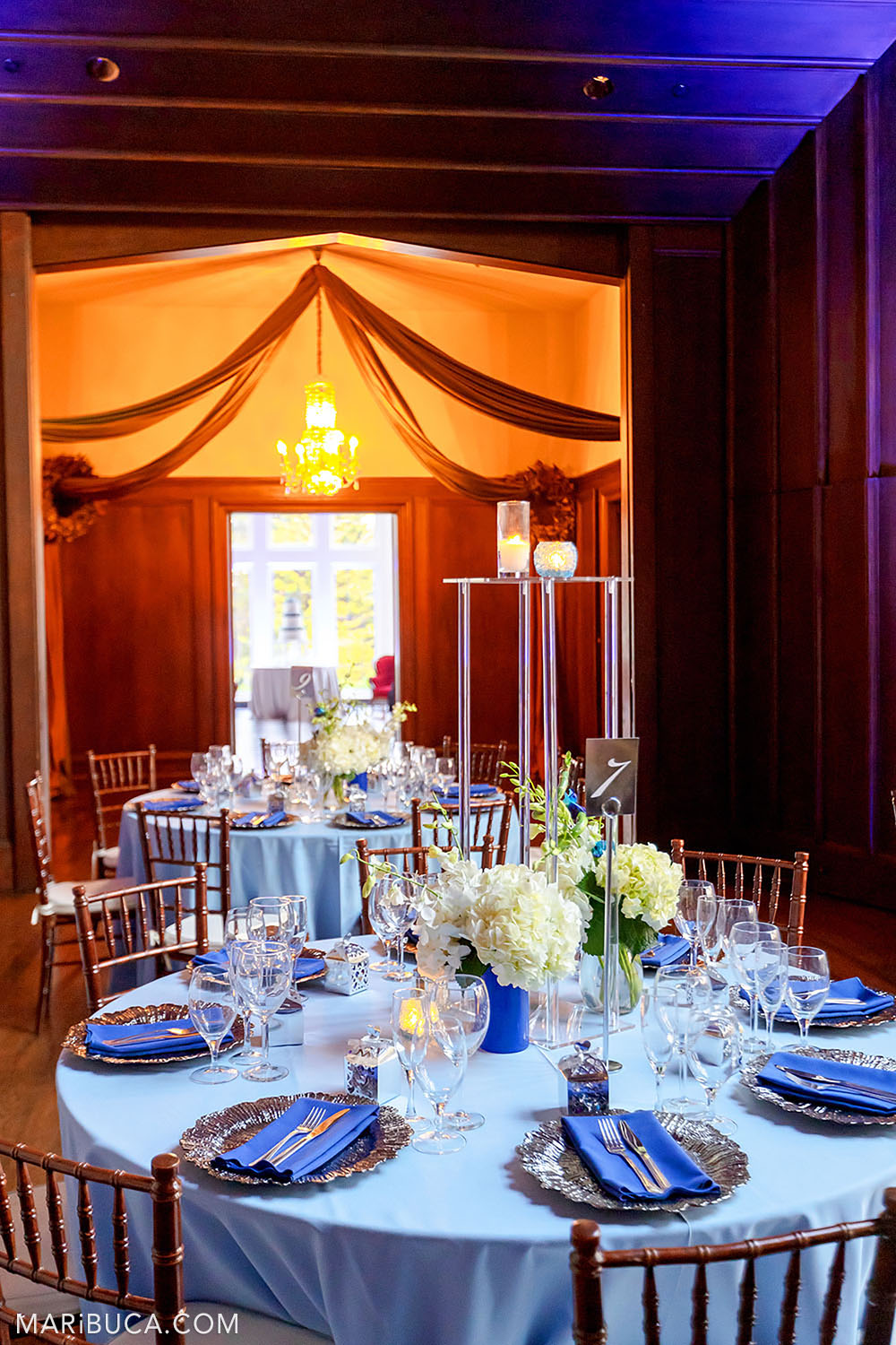 Wedding reception with rounded light blue table, navy blue cloth napkins, white bouquets of flowers and orange background in the Great Hall, Kohl Mansion, Burlingame