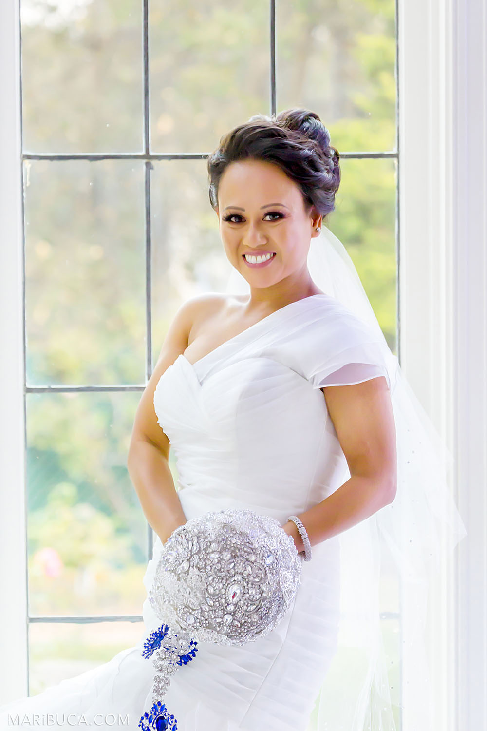 Portrait of the bride smiles and stays in front of big window with an amazing view in the Morning Room, Kohl Mansion, Burlingame