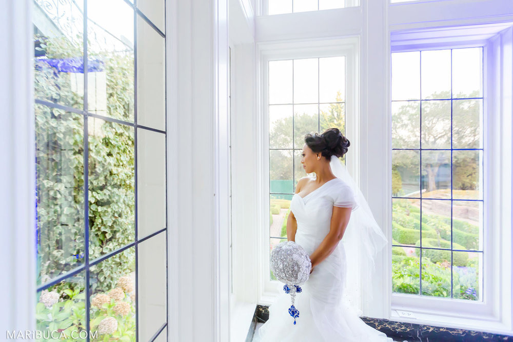 Beautiful bride look at the window with an amazing view on Rose Garden in the Kohl Mansion, Burlingame