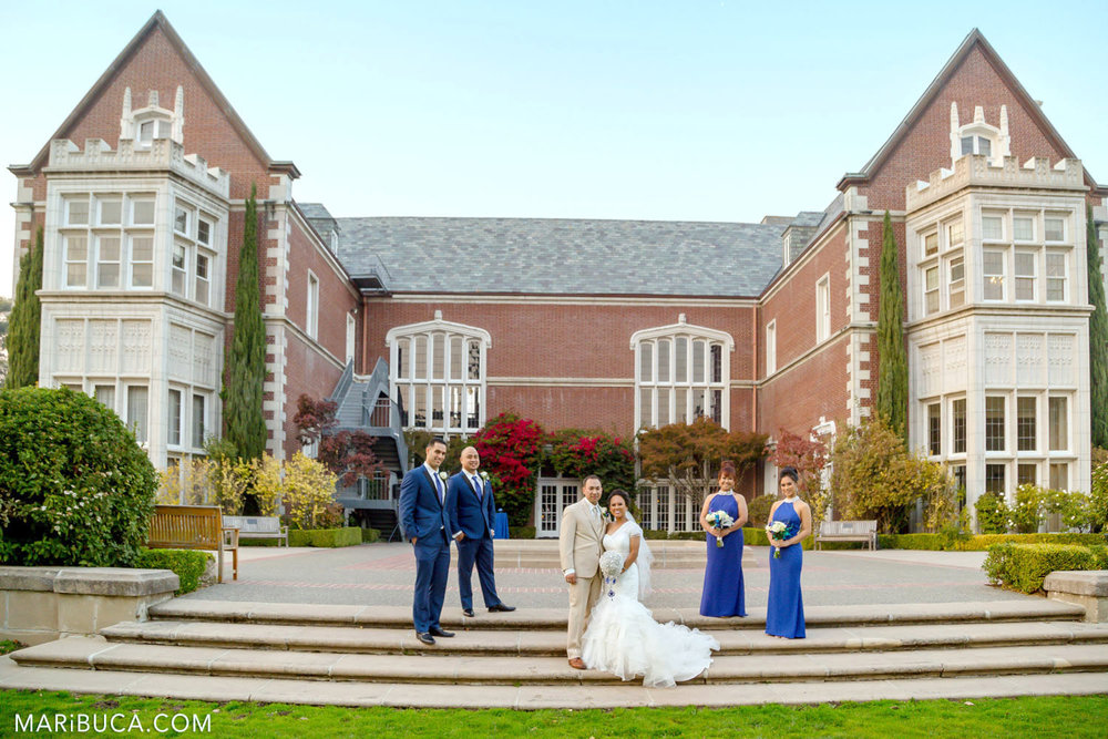 Bridal party dressed navy blue clothes and bride and groom dressed with light clothes surrounded Kohl Mansion building, Burlingame