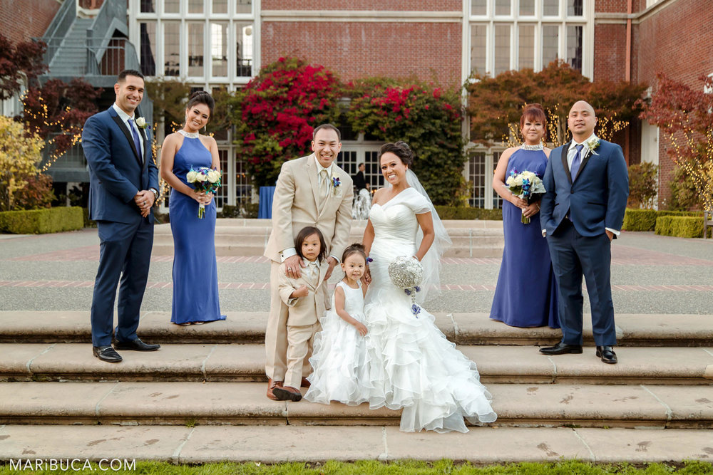 Bridal party dressed navy blue clothes and bride and groom includes two kids dressed with light clothes surrounded Kohl Mansion building, Burlingame