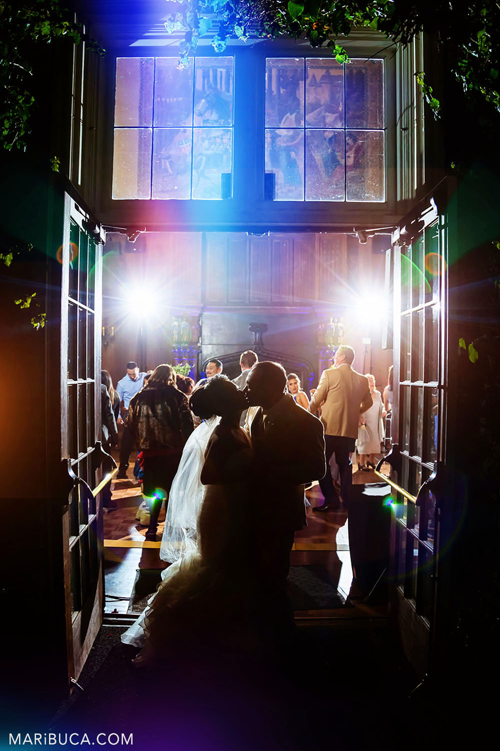 Bride and groom kiss each other surrounded by colorful lights and guests in the Great Hall, Kohl Mansion, Burlingame