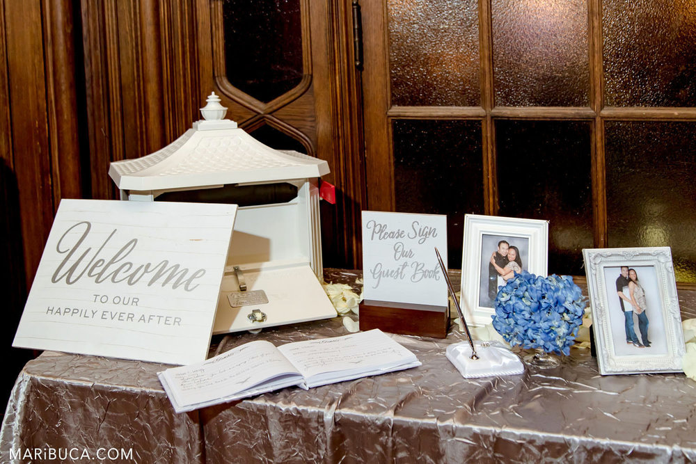 White Wedding decorations such as welcome sign, photos with newlyweds, guest book, box for gifts