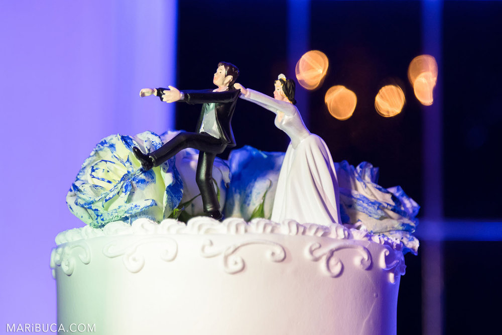 figure bride and groom on the cake: the bride is trying to keep the bride who wants to run on the background of purple and orange light bokeh.