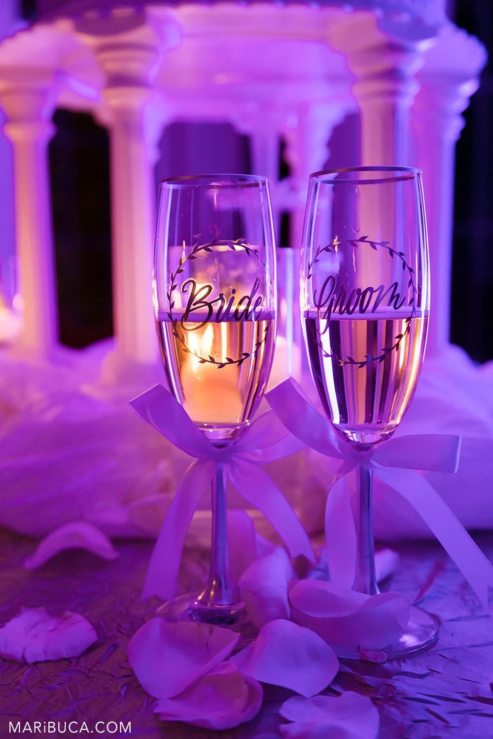 champagne glasses with the inscription: the bride and groom on a purple background