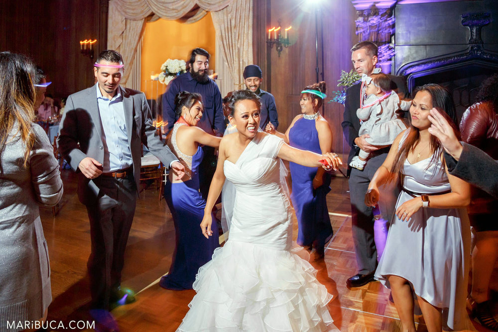 The bride and guests are dancing and laughing during the wedding reception in the Great Hall, Kohl Mansion, Burlingame