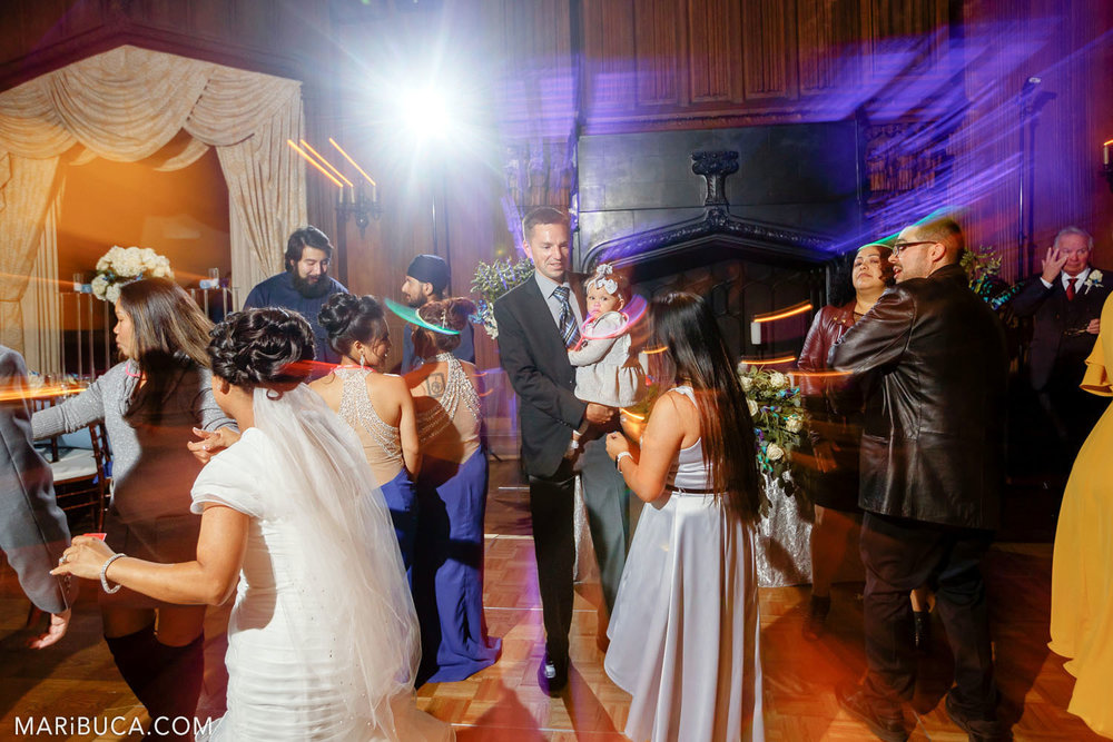 The bride and guests are dancing during the wedding reception surrounded orange - purple lights in the Great Hall, Kohl Mansion, Burlingame