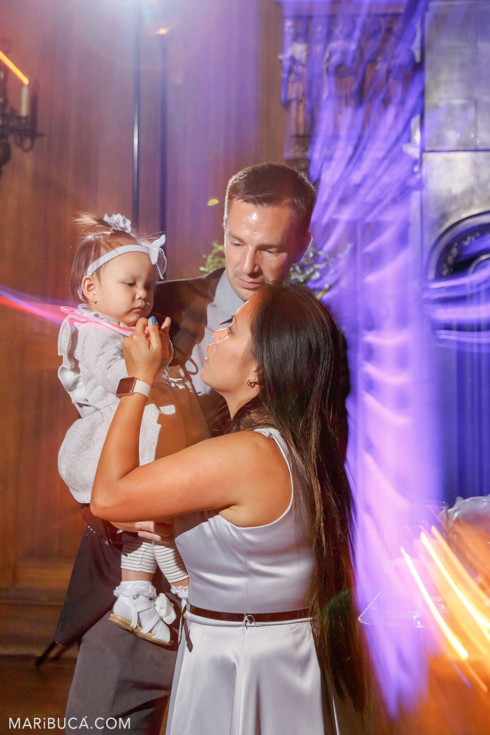 The bride and guests are dancing during the wedding reception surrounded orange and purple lights in the Great Hall, Kohl Mansion, Burlingame