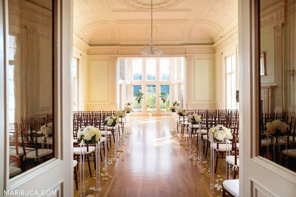 the white hall for the wedding ceremony is decorated with white flowers and high ceiling in the Dining room, Kohl Mansion, Burlingame