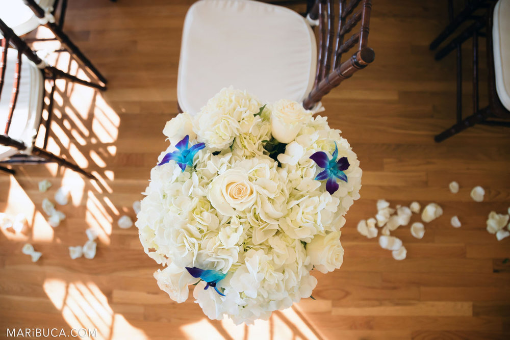 bouquet of flowers standing on the background of the wooden floor and white rose petals for wedding ceremony