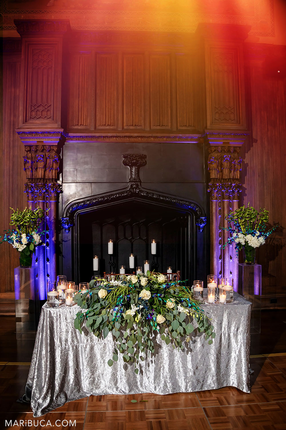 Bride and groom table with big beautiful white flowers surrounded fireplace with lit candles and purple and orange lights in the Great Hall, Kohl Mansion, Burlingame
