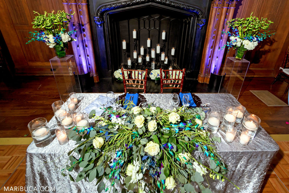 Newlyweds table with big beautiful white flowers surrounded fireplace with lit candles and purple and orange lights in the Great Hall, Kohl Mansion, Burlingame