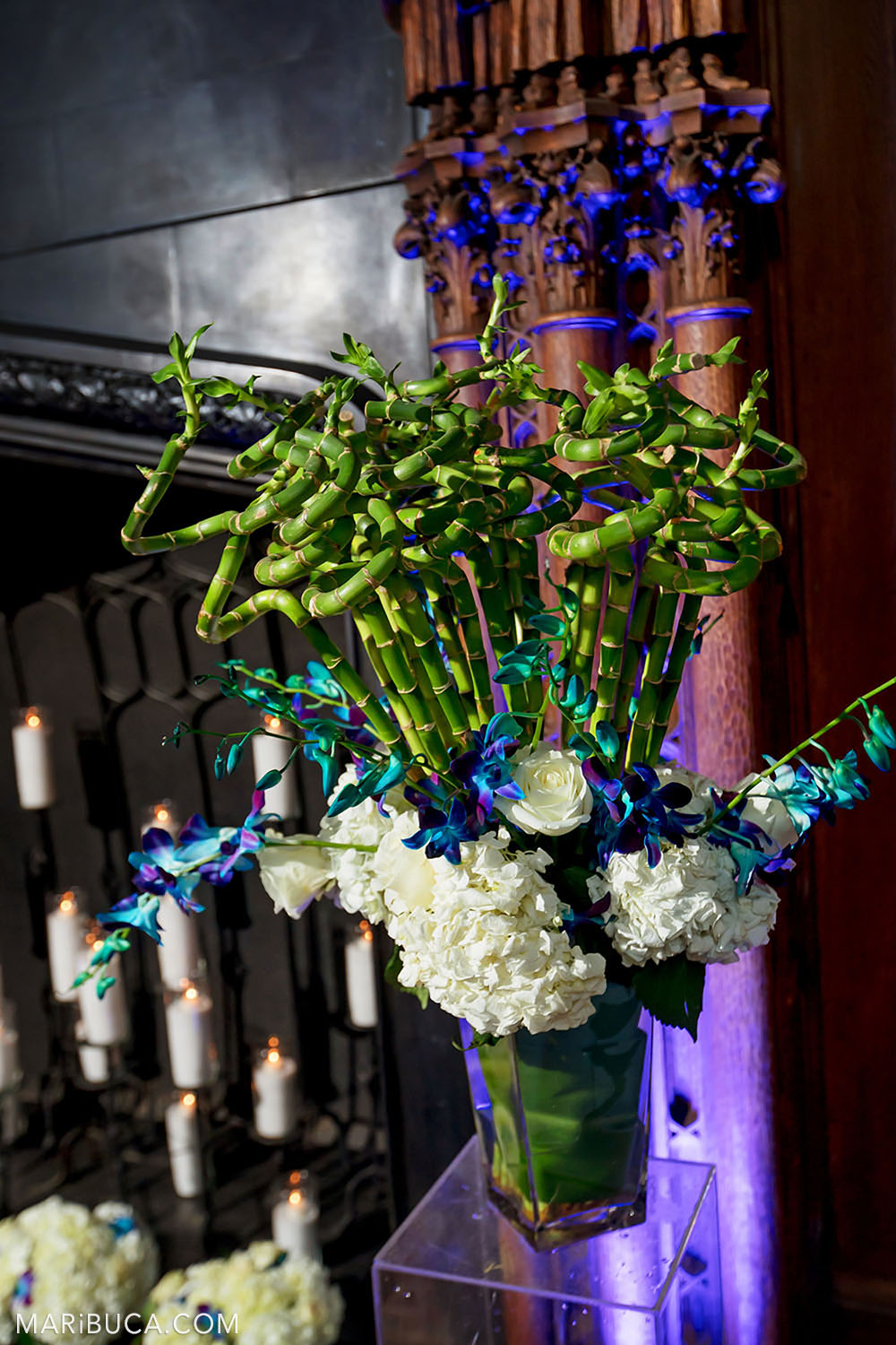 Wedding decoration: green grass bamboo, white flowers, lit candles and fireplace with purple light in the Great Hall, Kohl Mansion, Burlingame