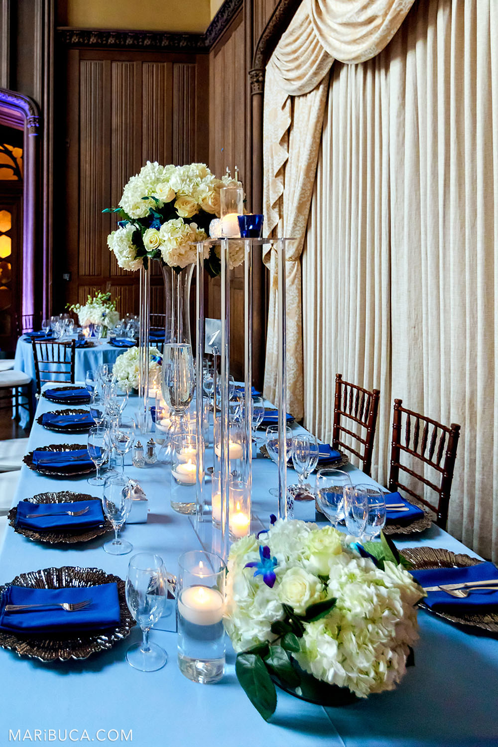 Wedding decoration blue theme: light blue tablecloths, blue towels for the guests, white bouquets with fresh flowers stay in the high glasses vases in the Great Hall, Kohl Mansion, Burlingame.