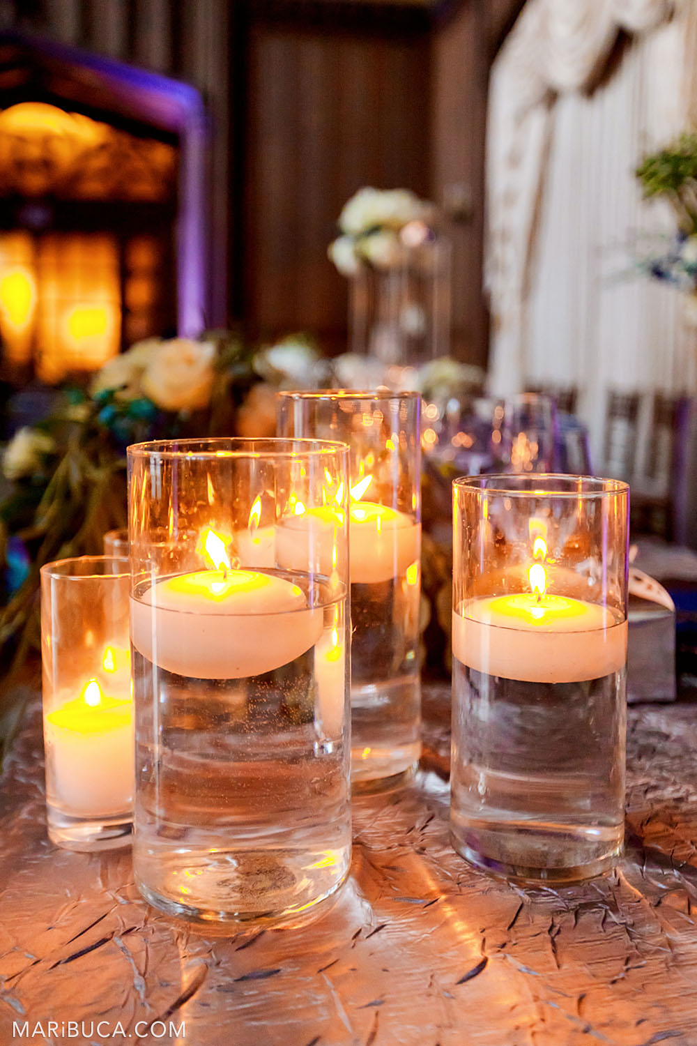 Wedding decoration: glass glasses of water are lit floating candles against the background of orange and purple lights in the Great Hall, Kohl Mansion, Burlingame