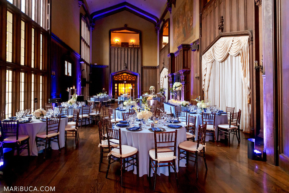 Wedding decoration of the Great Hall with brown walls and high ceilings such as round tables for guests in light blue tablecloths, white fresh flowers on them and a purple backlight in the background in the Kohl Mansion, Burlingame
