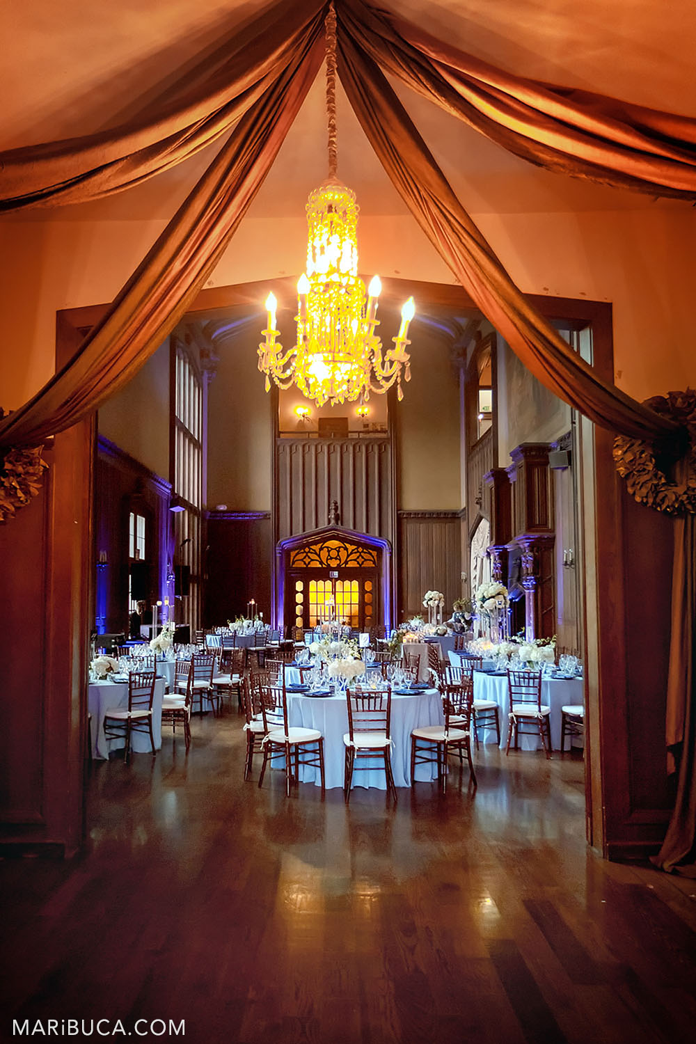 Wedding decoration of the Great Hall with brown walls and high ceilings such as round tables and light blue tablecloths, white fresh flowers on them and a purple backlight in the background in the Kohl Mansion, Burlingame