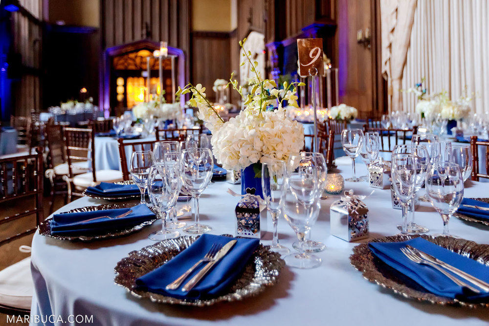 Wedding decoration of the Great Hall round tables for guests in light blue tablecloths, white fresh flowers on them and a purple backlight in the background in the Kohl Mansion, Burlingame