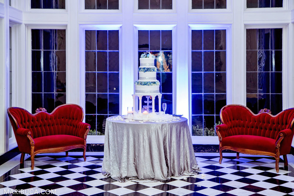 Wedding decoration of the Morning Room: 2 red couches, rounded table with silver tablecloth and big white-blue wedding cake in the Kohl Mansion, Burlingame